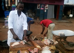 Roadside Fish Entrepreneur in Mukono, Uganda. Notice the two hand helps in the background.